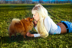 Girl with a dog. Pretty blond girl having a walk in the park with her dog Stock Images