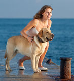 Girl with dog. Young woman with Labrador male dog on the coast of the sea Royalty Free Stock Image