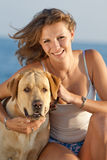 Girl with dog. Young woman with Labrador male dog on the coast of the sea Royalty Free Stock Photo