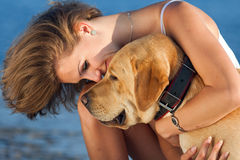Girl with dog. Young woman with Labrador male dog on the coast of the sea Stock Photo