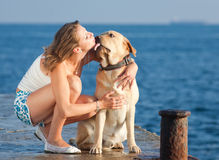 Girl with dog. Young woman with Labrador male dog on the coast of the sea Stock Images