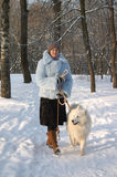 Girl with dog. Girl strolling with samoyed dog in winter park Royalty Free Stock Photography