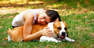 Girl and dog. Beautiful girl laying on an American Staffordshire Terrier dog outdoor in a park meadow Royalty Free Stock Image