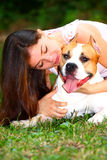 Girl with dog. Portrait of a beautiful girl holding , hugging  her dog (American Staffordshire Terrier) with her arms out in a park Stock Photo