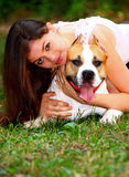 Girl and dog. Portrait of a beautiful girl holding her dog (American Staffordshire Terrier) in her arms close up shot portrait out in a park Stock Images