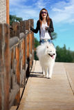 Girl with dog. A beautiful Asia girl with samoyed Royalty Free Stock Photos