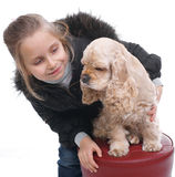 Girl and dog. Little girl in winter outwear lookong on american spaniel on white background royalty free stock photography