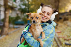 Girl and dog. Autumn. The girl is holding a small dog in her arms. Mistress and home pet for a walk in the autumn park. Caring for animals Royalty Free Stock Photo