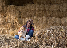 Girl with dog in barn. Pretty young country woman sitting on bales with dog in lap in barn Stock Photography