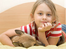 Girl with a dog on the bed Royalty Free Stock Photos