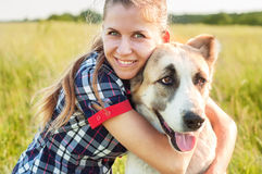 Girl and dog Central Asian Shepherd hug in a park. Walking with. A pet. Pedigree dog. Walking dogs. Dog happiness stock image