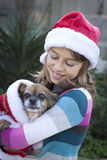 Girl and dog in christmas costume. A smiling girl in santa hat holding a small dog in a santa costume Stock Image