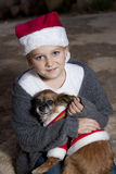 Girl with dog in christmas costumes. Girl dressed in christmas hat holding a dog with christmas costume Royalty Free Stock Photo
