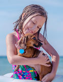 Girl and dog cuddle on beach. A cute little girl cuddles a small dachshund dog at the dog beach in Warren dunes park Michigan USA Royalty Free Stock Images
