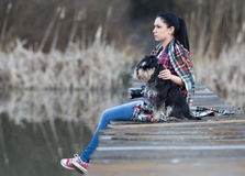 Girl with dog on the dock Royalty Free Stock Photography