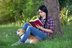 Girl with dog on grass, reading a book Stock Images