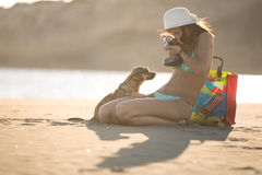 Girl and dog having fun on seaside.Cute neglected stray dog adopted by caring woman.Dog wearing sunglasses.Funny animal  Royalty Free Stock Images