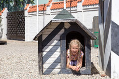 Girl in dog house Royalty Free Stock Photos