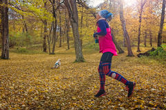 Girl and dog jogging and playing Royalty Free Stock Photography