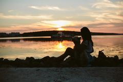 Girl and dog on the lake. On sunset background Stock Images