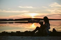 Girl and dog on the lake. On sunset background Stock Photography
