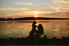 Girl and dog on the lake. On sunset background Stock Photo