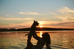 Girl and dog on the lake. On sunset background Royalty Free Stock Photos