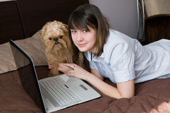 Girl with a dog and the laptop. The sixteen-year girl with a dog and the laptop on a bed royalty free stock photos