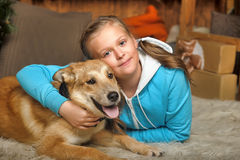Girl and dog lie close Stock Photos