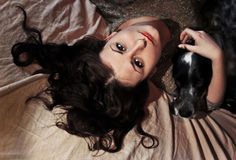 A girl and dog lying in bed stock photography