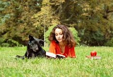 The girl and dog lying on a grass. In park Royalty Free Stock Images