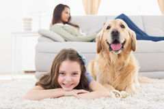 Girl with dog lying on rug at home Royalty Free Stock Photos