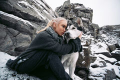 Girl with dog Malamute among rocks in winter. Close up. Royalty Free Stock Photography