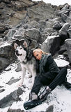 Girl with dog malamute among rocks in winter. Royalty Free Stock Images