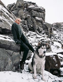 Girl with dog Malamute among rocks in winter. Royalty Free Stock Image