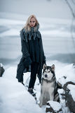 Girl with dog Malamute among rocks in winter. Stock Photography