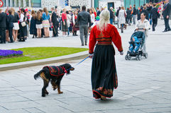 The girl and dog at norwegian constitution day. The girl in national norwegian dress and dog at norwegian constitution day royalty free stock images