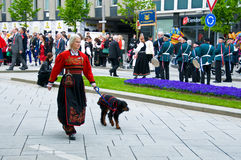 The girl and dog at norwegian constitution day during parade. The girl in national norwegian dress and dog at norwegian constitution day during parade royalty free stock photography