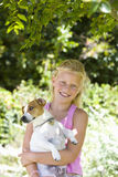 Girl (8-10) with dog outdoors, smiling, portrait Stock Photo