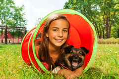 Girl with dog play in playground tube Stock Photo
