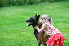 Girl with dog. Girl playing with dog on grass Royalty Free Stock Image