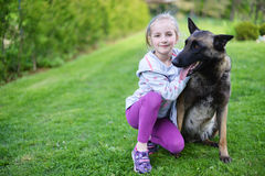 Girl and dog. Girl playing with dog on grass Royalty Free Stock Image