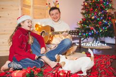 Girl with a dog playing the guitar and singing near christmas tr Royalty Free Stock Photos