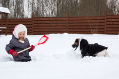 Girl and dog playing in snow with a shovel royalty free stock photos