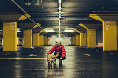 Girl with a dog in the public garage Stock Photos