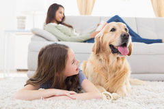 Girl with dog on rug at home Royalty Free Stock Photography