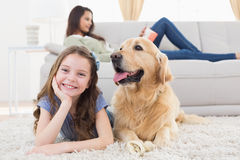 Girl with dog on rug while mother relaxing at home Stock Image