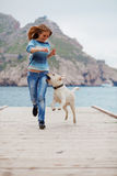 Girl with dog running Royalty Free Stock Images