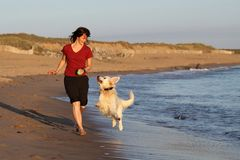 Girl and dog running on beach Stock Image