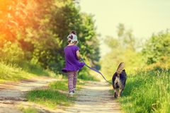 Girl with dog running on the dirt road Stock Images